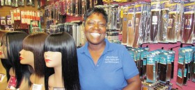 MONEY—Nora Johnson, of Sisters Beauty Supply, poses with hair pieces, some of her largest moneymakers. (Photo by J.L. Martello)
