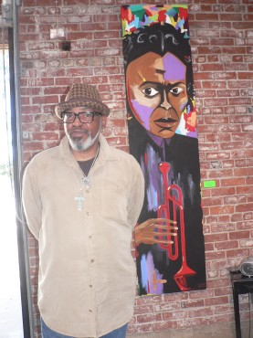 "Artist Gerry ""GOS"" Simpson stands in front of one his paintings of jazz trumpeter Miles Davis. Simpson's A Touch of Jazz exhibit was on display at the Brickhouse Art Gallery in Oak Park (OBSERVER photos by Antonio R. Harvey)."