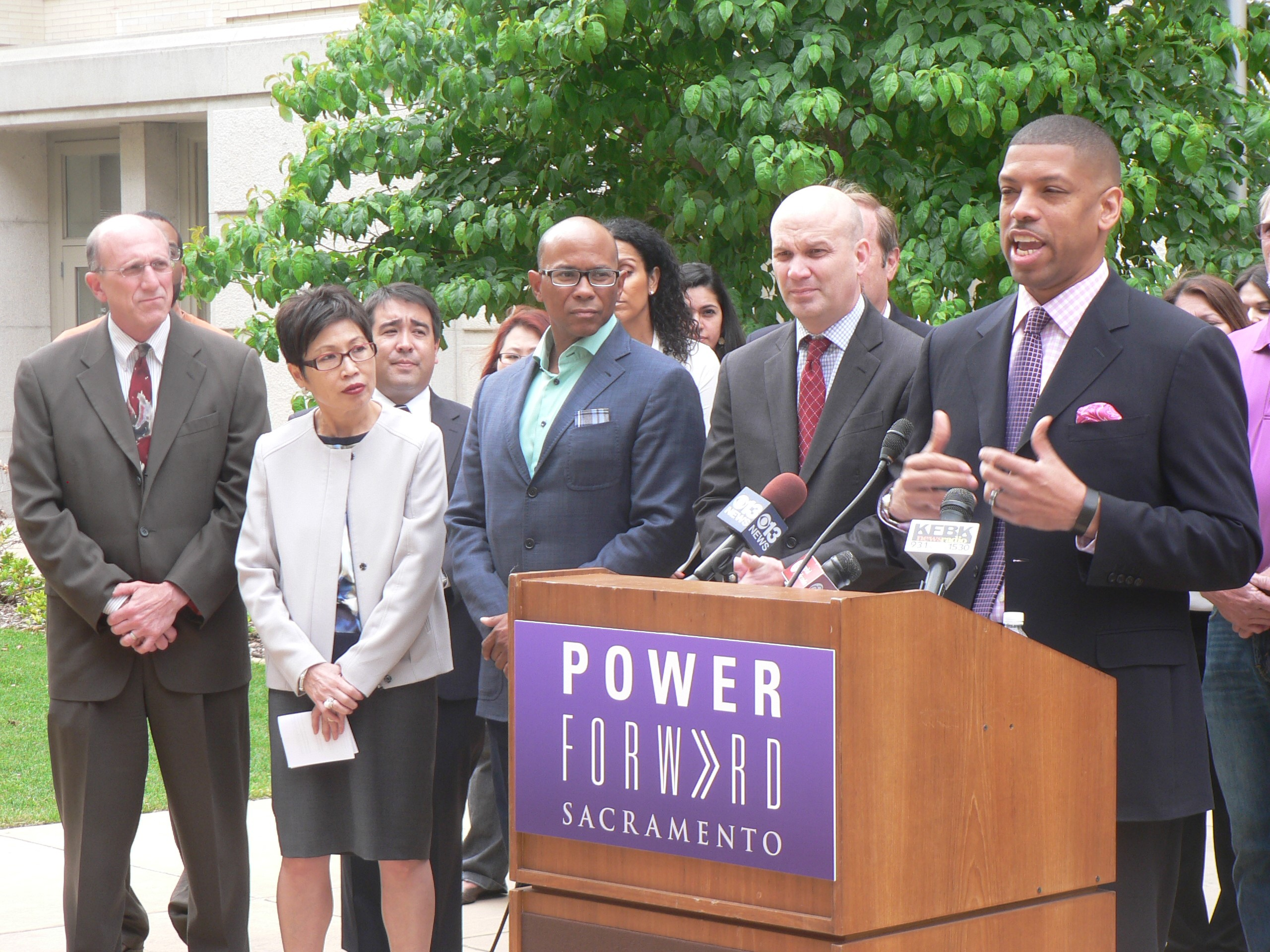 Mayor Kevin Johnson, at podium, has been a driving force behind the downtown arena development. Here Mayor Johnson is shown with, from left to right, City Councilmember Jay Schenirer, Asian Chamber of Commerce CEO Pat Fong-Kushida, City Councilmember Allen Warren and Sacramento Kings President Chris Granger.