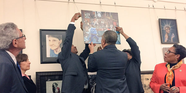 CBC members hang student's artwork after it was removed by a Republican congressman. (Lauren Burke/NNPA)